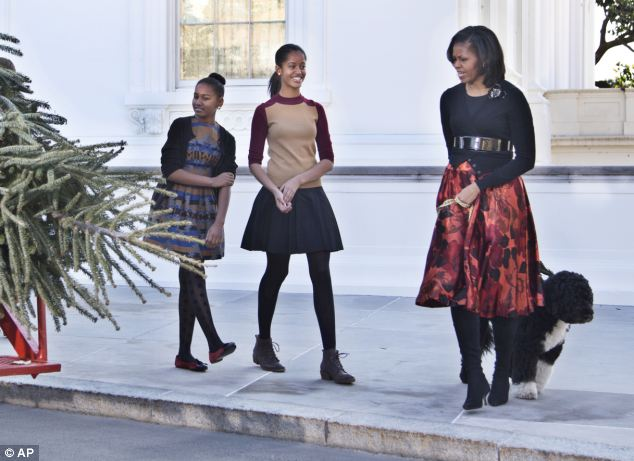 Festive: The family smiles as they look at the tree, which will be placed in the Blue Room of the White House