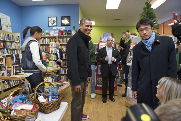 President Barack Obama, with daughter Malia, (left), goes shopping at a small bookstore, One More Page, in Arlington, Virginia today