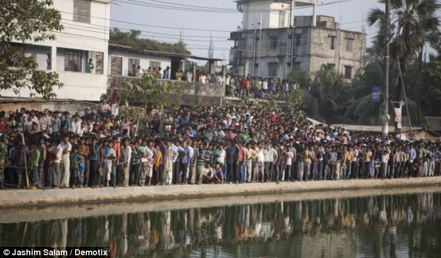 Onlookers: Crowds gather to watch the search and rescue effort in Chittagong