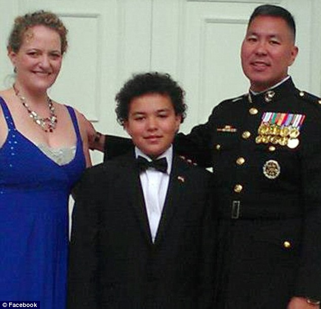 Major George Anikow (right), and inactive Marine, was stabbed to death in Manila at the weekend. Here he is pictured earlier this month in uniform at a ball with his wife Laura, a U.S. diplomat, and Jacob one of his three children