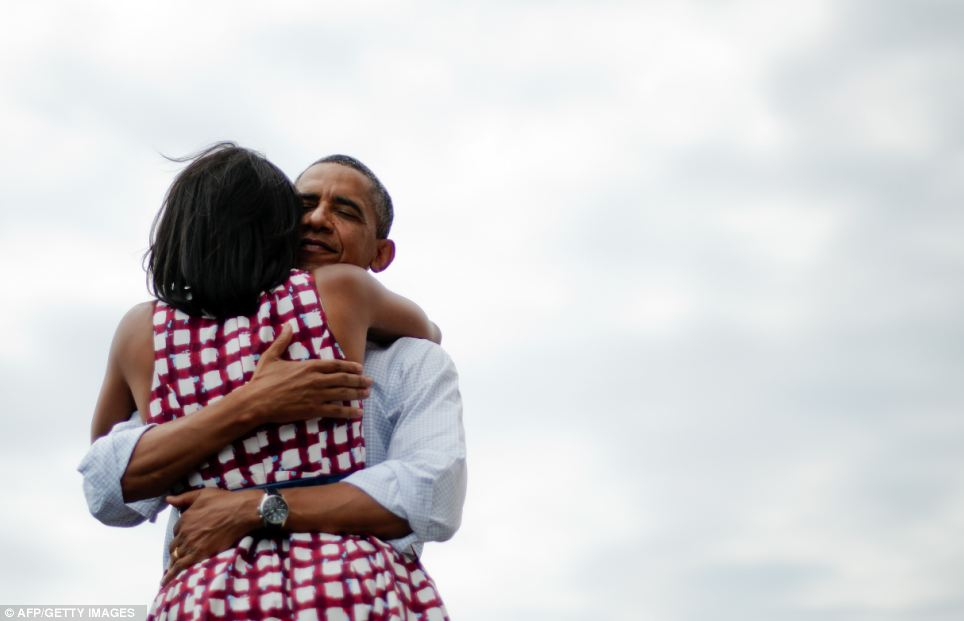 First Lady Michelle Obama and US President Barack Obama hug after delivering remarks during a campaign event in Iowa last August