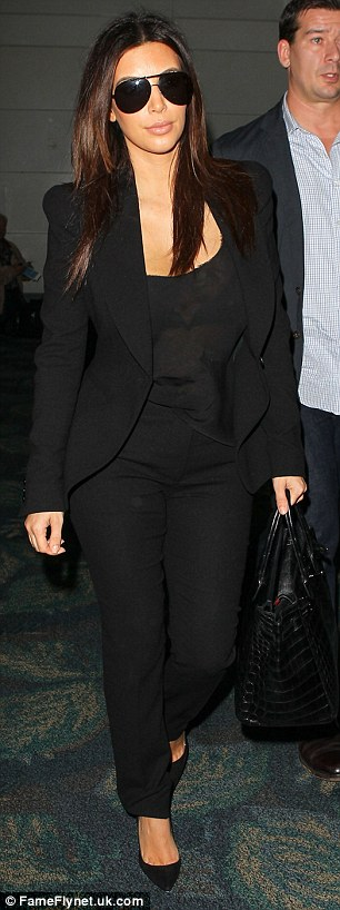 KiSuits you: The brunette star opted for a black trouser suit, which flattered her famous curves