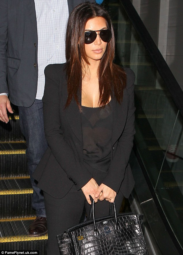 Sheer daring: Kim displayed her V-shaped bra through a sheer black top as she jetted out of Fort Lauterdale airport on Tuesday