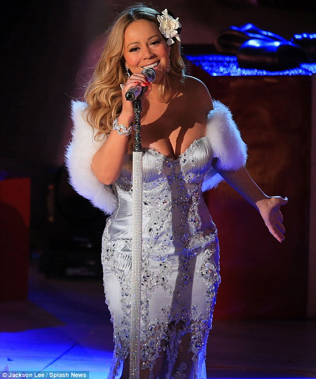 Silver bells: Mariah also donned a wintry silver gown and fur for another number