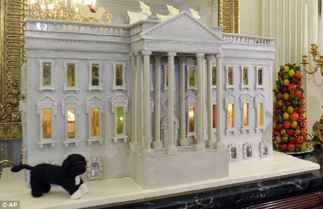 Looking good enough to eat: A 300lb gingerbread replica of the White House is the centrepiece of the White House Christmas decorations, unveiled today by Michelle Obama