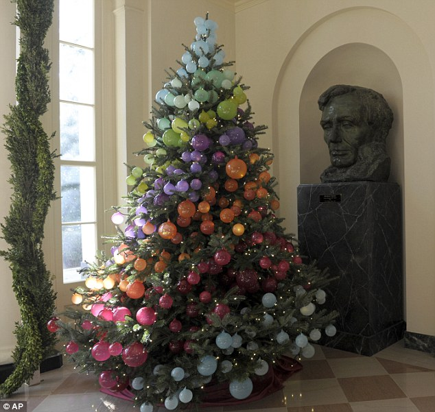 Festive spirit: A Christmas tree decorated in a rainbow of colors sits next to a statue of President Lincoln in the East Garden Room of the White House