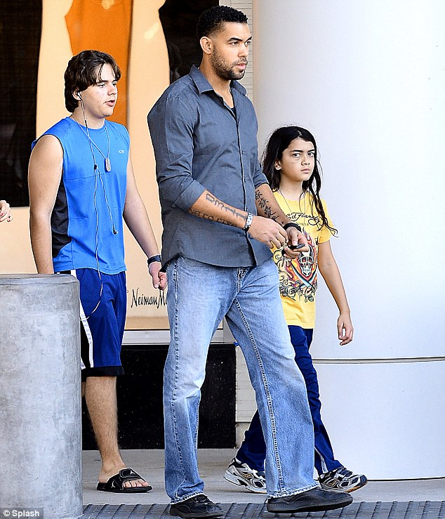 Boys only: Prince and Blanket head out to the shops with their heavily tattooed bodyguard