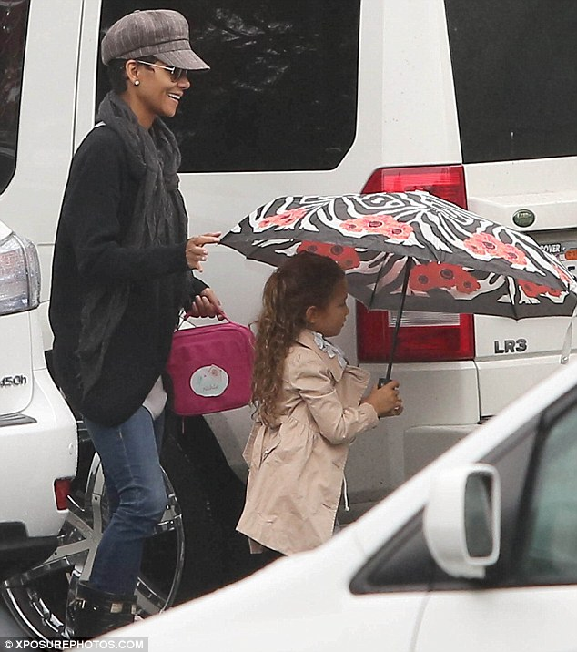 Spring in her step: Halle appeared to be more upbeat as she stepped out in the rain with Nahla, who came prepared with an umbrella