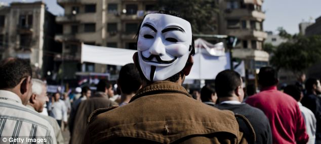Face-off: Some protestors yesterday wore masks, such as this man, who has an 'anonymous' mask on the back of his head