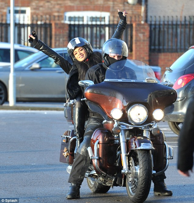 Show stopper: Nicole was enjoying her moment on the back of a bike as she threw her hands up in the air