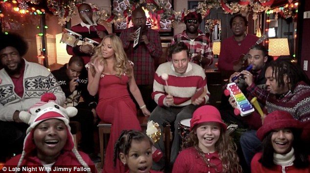 Christmas capers: The singer was accompanied by hip-hop band The Roots and a troupe of small children