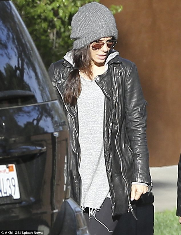 Spot the star: Sandra appeared to be attempting to go incognito in her woolly hat and oversize aviator sunglasses