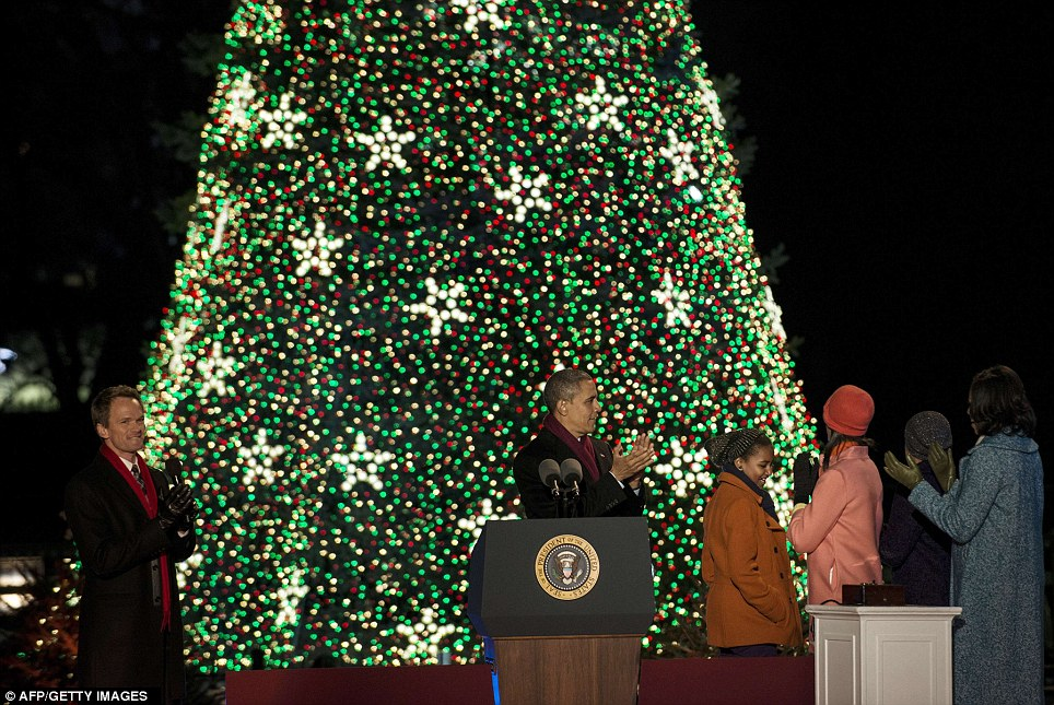 A little help from friends: Actor Neil Patrick Harris, left, hosted Thursday night's ceremony as the Obamas flipped the switch to the blue spruce