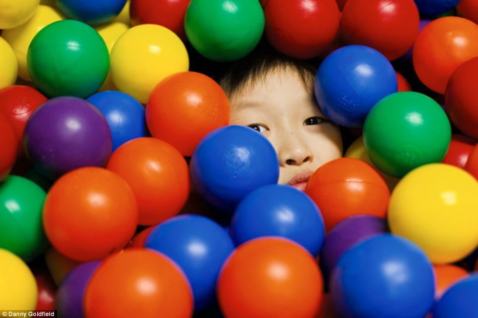 Camera shy? Ethan from South Korea hides in a ball pond as the photographer, who lives in New York, snaps away