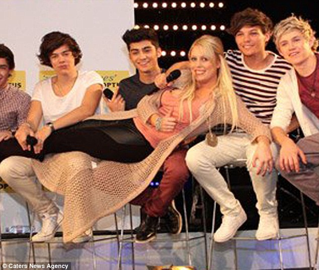 Pose: DJ Mel Greig lies across the laps of One Direction when they flew into Australia this year