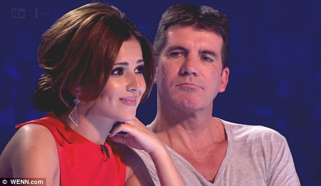 Big money: Cheryl Cole, pictured with Simon Cowell on X Factor UK, was dumped from the US version of X Factor and now she's suing the show's producers for more than $2.3 million