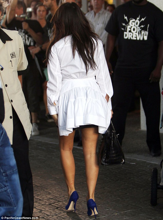 Leaving the competition behind: Wearing an unusual shirt, Kim kept her famous derriere underwraps during her trip to the Bal Harbour mall