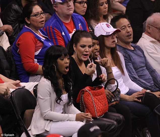 I'm watching! Khloe combines cheering with plumping up her lips with some gloss