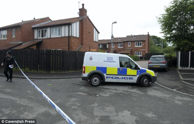Investigation: Police outside Esther Arogundade's Salford home where she was murdered in June last year