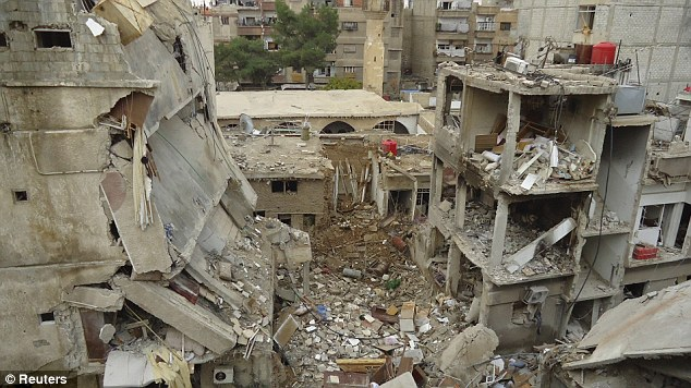 Rubble: A collapsed building is pictured following what activists said were airstrikes by a Syrian Government fighter jets in Daraya, near Damascus