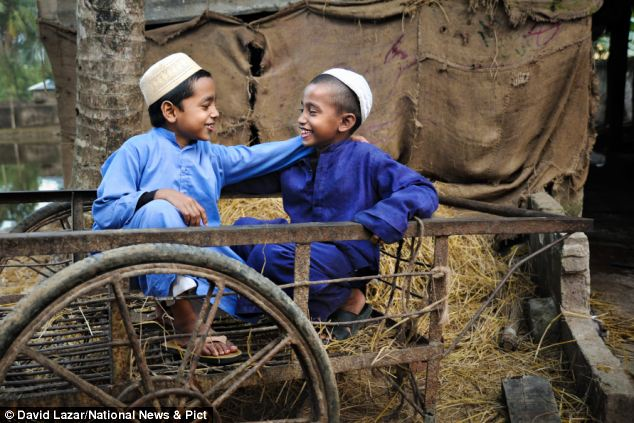 Best of friends: Two students of a Madrasah Islamiah in Srimangal, take some time out of their studies and play in the field next to their mosque