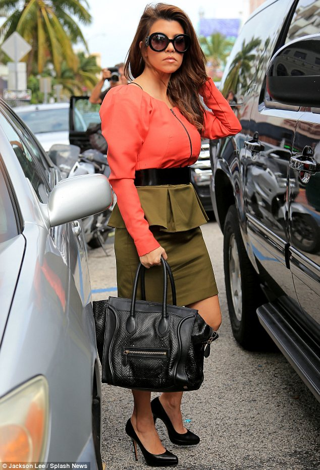 Keeping it chic: Meanwhile Kourtney looked fashionable as she paired her olive skirt with a structured coral top