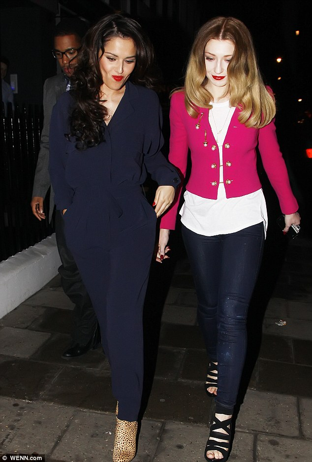 Boiler suit chic: Cheryl Cole fades into the background in her navy jumpsuit as Nicola Roberts brightens up the evening with her pink jacket