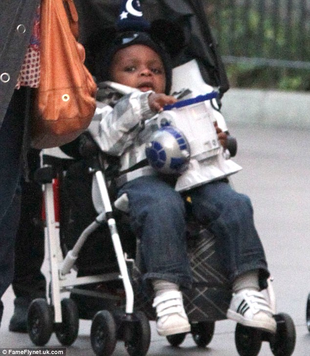 Happy baby: Louis seemed content in his buggy, clutching a toy while enjoying the sights of the theme park
