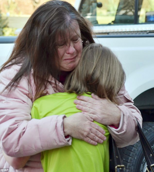 A mother hugs her daughter following a shooting at the Sandy Hook Elementary School, Conn., on Friday