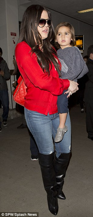 Lady in red: Khloe made sure she was easily spotted as she made her way through the airport donning a bright red shirt