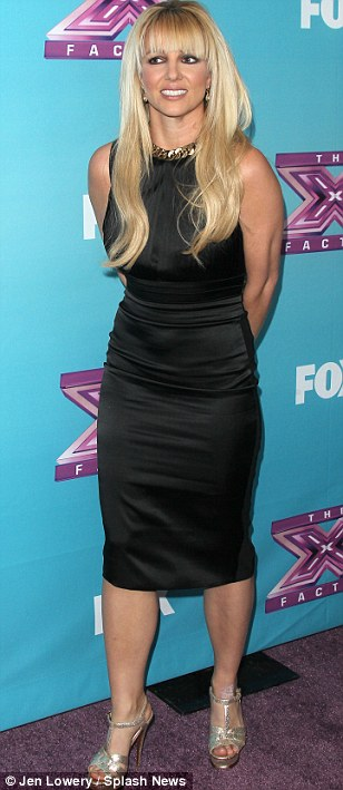 Little black dress: Britney looked happy and relaxed in a clinging black sleeveless midi dress and gold heels