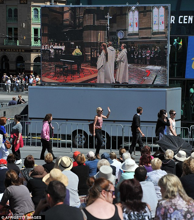 Mourners gather to watch the memorial service on big screens in Melbourne's Federation Square