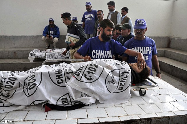 Rescue workers move the bodies of two of the Polio vaccination workers to a mortuary after four female polio vaccination workers were killed in Karachi, Pakistan, today