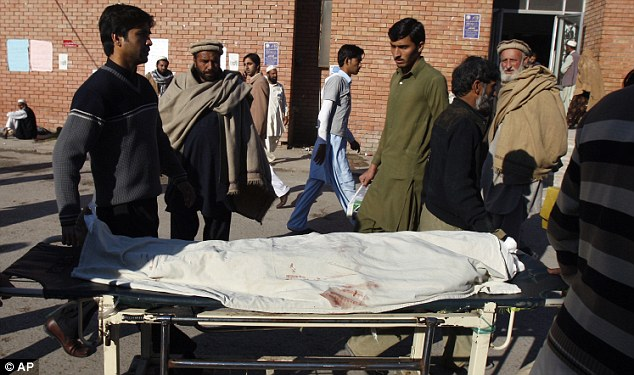 Pakistani relatives transport the dead body of a female polio worker who was killed by gunmen at a local hospital in Peshawar, Pakistan