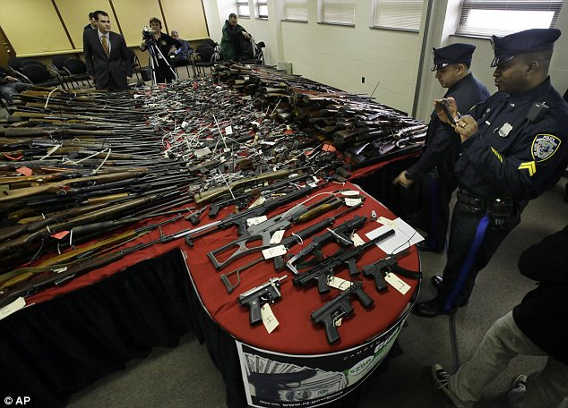 Taking a closer look: Camden police officers examine and take photos of guns displayed on tables at police headquarters