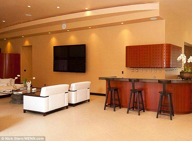 To the bar: Another lounging area boasts enough wall space for a gargantuan flat screen television, and several seats at the bar