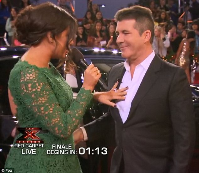 Quite the welcome: Khloe greeted Simon Cowell on the red carpet by stroking his chest