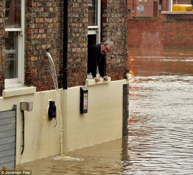 A man at the Lowther pub leans out of a window and watches water as it is pumped out of the building