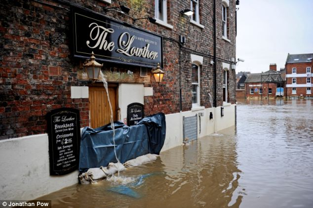 Homes and businesses are boarded up to try and stop the water from destroying property