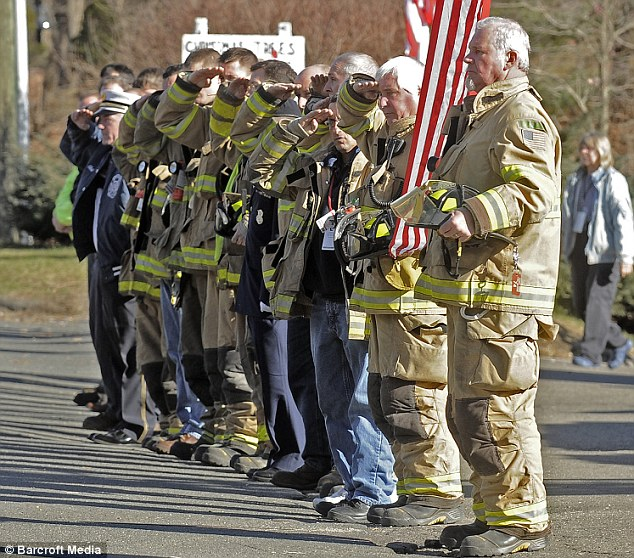 Protectors: Fireman salute at a funeral in Newtown as Michelle Obama praised the bravery of first responders