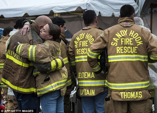 Rescue: Members of the Sandy Hook Volunteer Fire and Rescue department hug after a moment of silence in Sandy Hook village