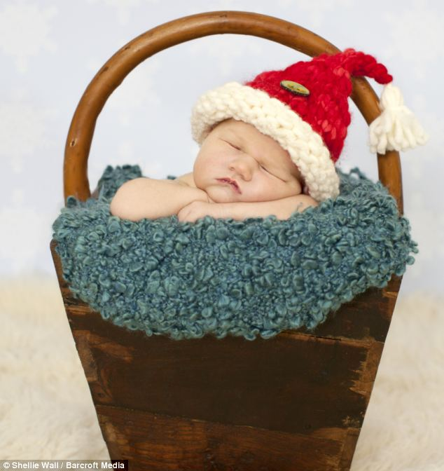A newborn baby sleeps wearing a Santa hat while inside a Christmas hamper - and looks deep in sleep