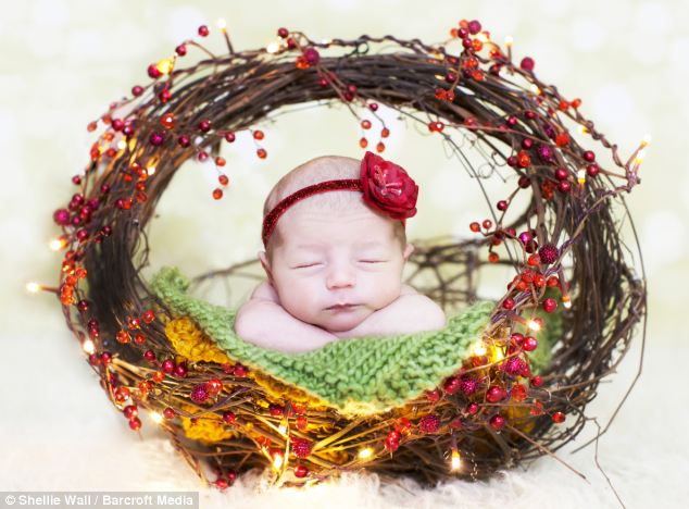 Festive photo: A peaceful newborn baby sleeps inside a twinkling Christmas wreath
