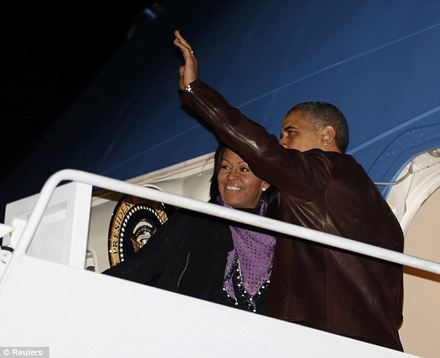U.S. President Barack Obama waves next to first lady Michelle Obama as they prepare to depart Joint Base Andrews outside Washington, for their holiday trip to Hawaii