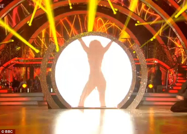 Stunning silhouette: Kimberley disappeared behind a white backdrop as she stripped off her catsuit