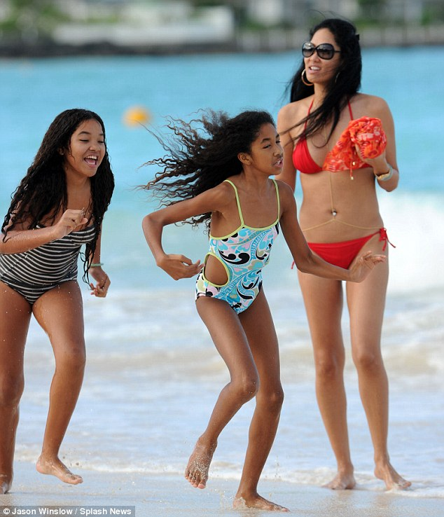 Simmons sisters: Ming, who turns 13 next month, was all smiles in her black-striped one-piece, while her 10-year-old sister wore a blue patterned bathing suit with cut-outs on each side