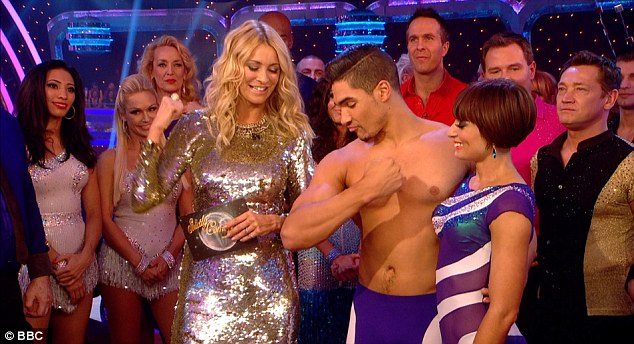 Louis, pictured with dance partner, shows his muscle to Strictly Come Dancing presenter Tess Daly