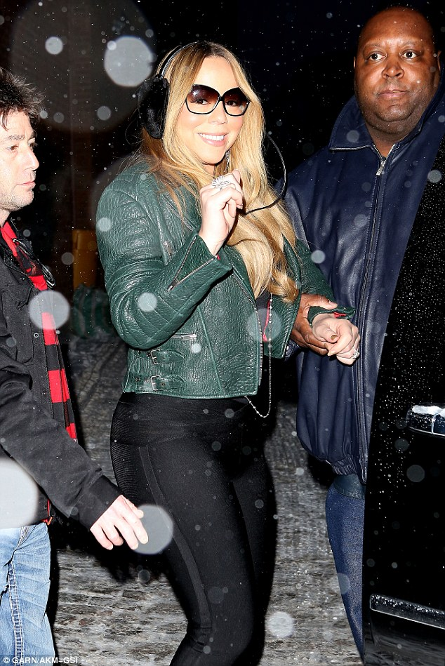 They've got her back: Mariah was buffered by not one but two bodyguards as she made her way to her waiting vehicle