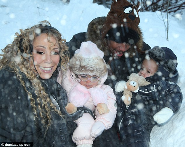 Happy times: In several shots, the entire grinning clan is bundled up in fur-lined snowsuits enjoying a cuddle puddle on the snowy ground