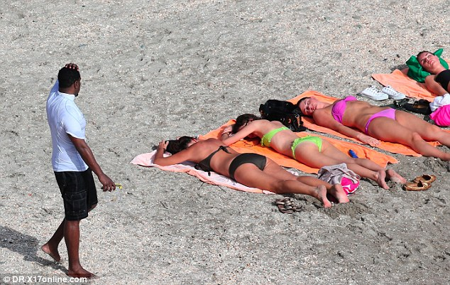 Looking for a date? P Diddy scratches his head as he eyes up a row of sleeping sunbathing beauties on the beach in Gustavia in St Barts
